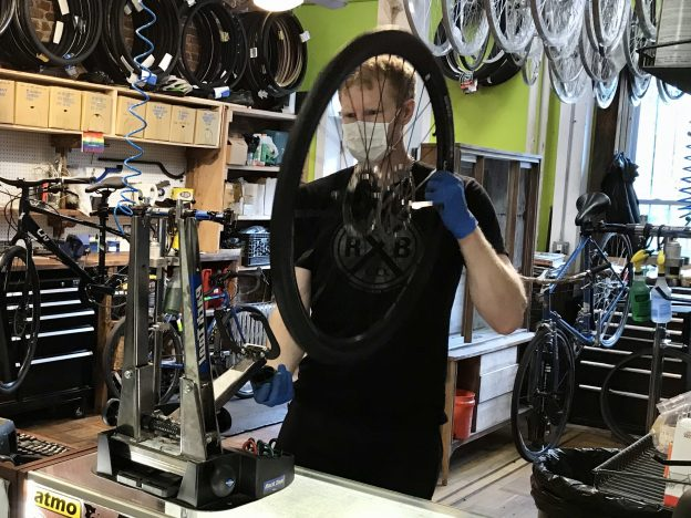 A mechanic at Bicycle Roots Bike Shop trues a wheel while wearing a face mask and gloves